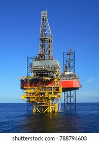 Drilling rig and production platform with blue sky background in oil and gas field