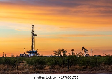 Drilling rig and pump jack sunset
