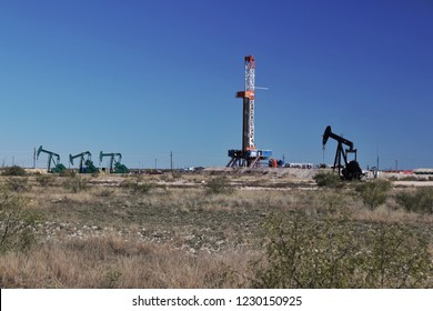 Drilling rig and pump jacks in West Texas