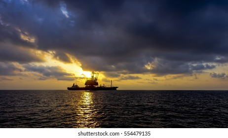 Drilling rig silhouette in sunset ocean