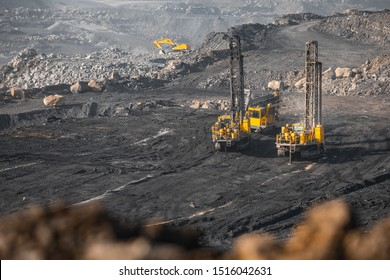 Drilling rigs borer drill wells for installing cast explosives blasting. Open mine coal and minerals from bowels soil explosion.