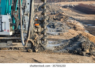 Drilling tractor installs concrete piles in the ground at construction site. Selective focus.