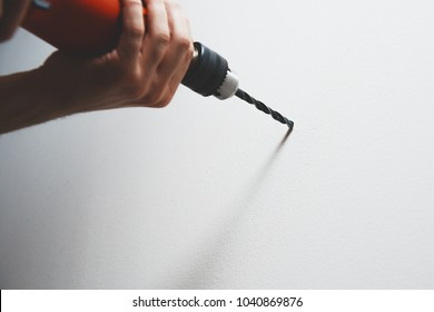 Drilling in the wall. The man is holding a screwdriver or drill in hand. Drills a hole in the wall using a drill with a drill. Concept of housework, renovation at home, apartment.