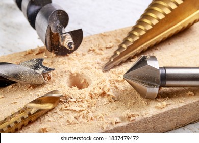 Drilling in wood with steel drills and countersinks. Minor carpentry work in the workshop. Light background.