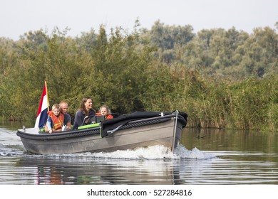 """DRIMMELEN, NETHERLANDS - OCTOBER 3, 2015: Family with children sailing a touristic boat in National park """"the Biesbosch"""" in the Netherlands"""