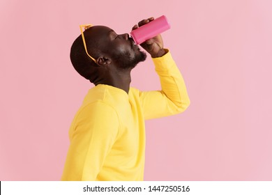 Drink. Black man drinking soft drink on pink background. Colorful portrait of happy smiling african american male model in yellow fashion clothes enjoying soda from pink can in studio
