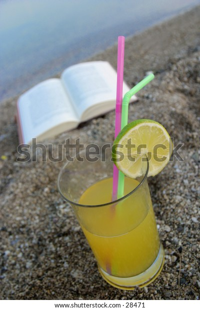 a drink and a book on the beach,drink in focus book a bit burry