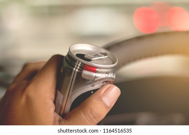 Drink coffee while driving.,Guy drinking canned coffee while driving
