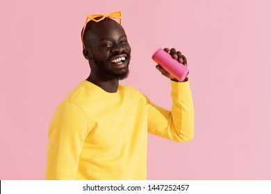 Drink. Colorful portrait of happy black man drinking soft drink on pink background. Cheerful smiling young african american male model in yellow fashion clothes holding pink soda can in studio
