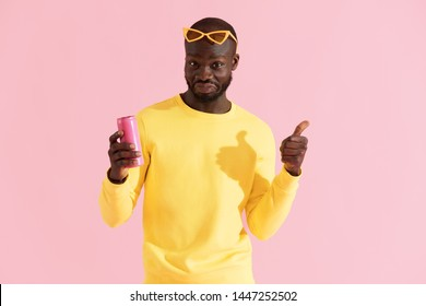 Drink. Colorful portrait of happy black man with soft drink showing like on pink background. Smiling young african american male model in yellow fashion clothes holding pink soda can in studio