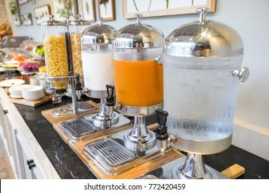 Drink corner in hotel buffet line, selective focus on orange juice