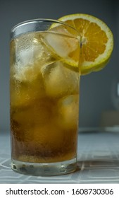 Drink Cuba libre with ice, decorated with an orange slice in a tall glass