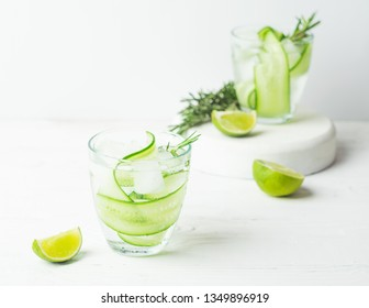 Drink from fresh cucumber juicy lime and a sprig of rosemary in glass glasses on a white background. Summer refreshing detox. Selective focus. Horizontal frame.