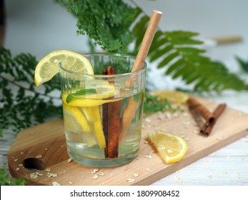 Drink with lemon and cinnamon sticks on a wooden board