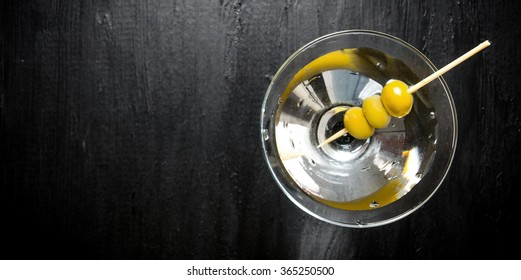Drink martini. Martini with olives on a black table. Free space for text. Top view
