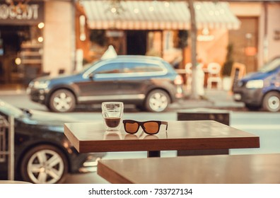 Drink on a table in a street cafe with moving cars and bright store showcases.