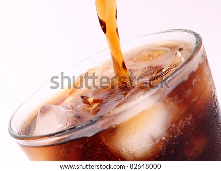 drink poured into a glass over white background