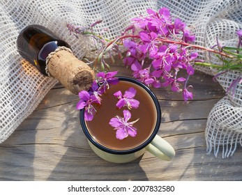 Drink, tea in a mug, chamerion angustifolium with pink flowers on a wooden table, flat layout. Useful plant epilobium parviflorum for use in herbal alternative medicine, homeopathy and cosmetology