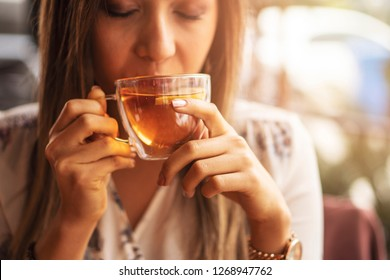 Drink Tea relax cosy photo with blurred background. Female hands holding mug of hot Tea in morning. Young woman relaxing tea cup on hand. Good morning Tea or Have a happy day message concept
