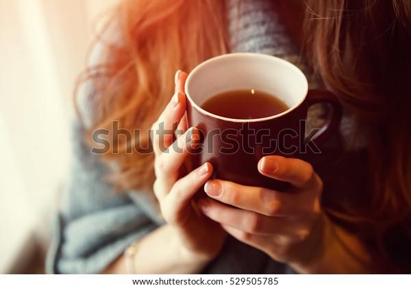 ぼかした背景に心地よい写真を使って、お茶を飲みましょう。朝に熱いお茶のマグを持つ女性の手。茶碗を手に持ってくつろぐ若い女性。おはようお茶か、おめでとう日のメッセージのコンセプト。