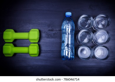 Drink water concept. 2 litres of mineral water in glasses and bottle, green dumbells on black wooden background for weight loss and good metabolism, top view