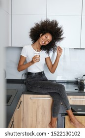 Drink water. Happy young woman with glass of fresh water in white kitchen portrait. Beautiful smiling african american girl drinking pure mineral water in morning at home