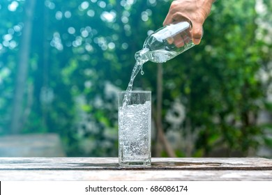 Drink water pouring in to glass over sunlight and natural green background.Select focus blurred background.