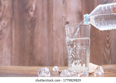 Drink water pouring into glass on wood table and space for text