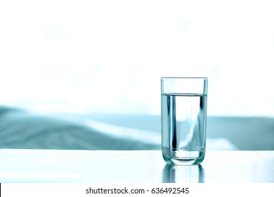 Drink Water.  Pure water in the glass on the table at luxurious bedroom. Health concept