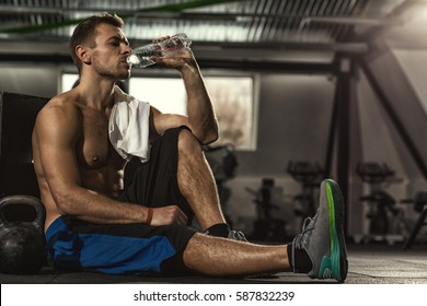 Drink water. Shirtless sportsman resting after training at the gym sitting on the floor drinking water with his eyes closed copyspase pleasure resting relax sports water lifestyle hydration vitality
