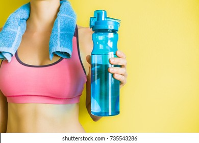Drink water, stay hydrated concept. Fitness woman holding up bottle of water.