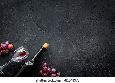 Drink wine concept. Bottle, glass, grape on black background top view copyspace