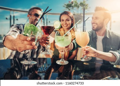 Drink for you. Close up of various cocktails in people hands. Company sitting at the table of outdoor bar