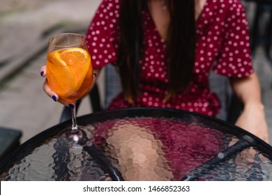 Drinking aperol spritz at summer terrace. Elegant woman drinking iced summer cocktail
