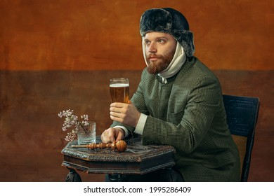 Drinking beer. Portrait of red headed and bearded man playing famous artist Van Gogh isolated on dark orange bacground. Concept of art, eras comparison, fashion. imitation, humor, ad. Bandaged ear. - Shutterstock ID 1995286409
