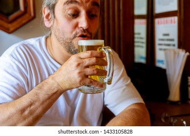 Drinking beer. Side view of handsome man drinking beer while sitting at the bar counter