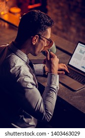 Drinking cappuccino. Elegant businessman drinking cappuccino and working on laptop in his own restaurant
