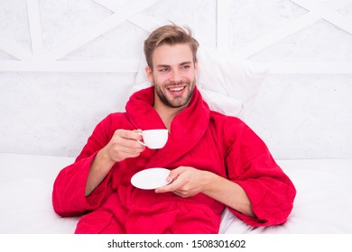 Drinking coffee for breakfast. Happy guy drinking coffee in bed. Bearded man in bathrobe holding drinking cup and smiling. Enjoying drinking tea or other hot beverage after bath spa.