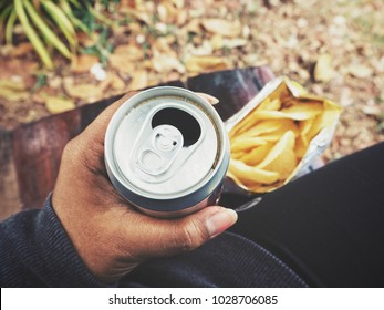 Drinking cola on hand with potato chips