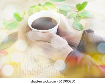 Drinking cup of coffee with two hands with colorful bokeh background