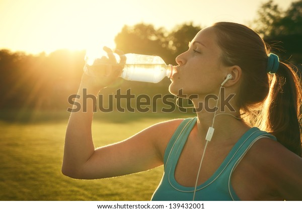 Drinking during sport / Young woman drinking water after run