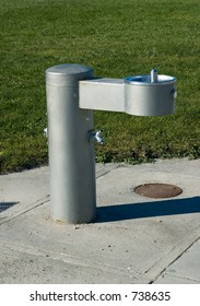 Drinking fountain in park installed in a sidewalk on the edge of the grass.