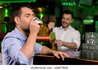 Drinking a freshly tapped beer. Handsome young man drinking beer while bartender tapping beer on the background