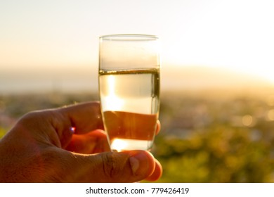 Drinking a glass of champagne in front of a marvelous landscape at sunset time, celebrating with happiness