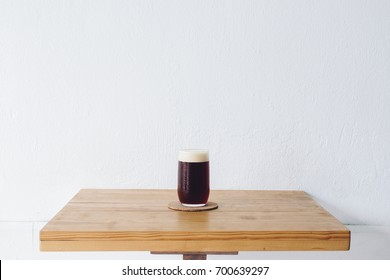 A drinking glass of cold brew dip coffee on the table with white wall background.
