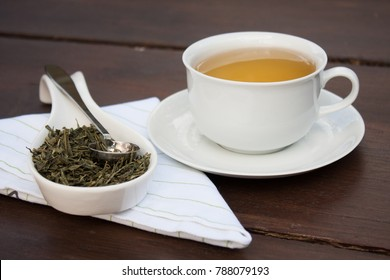 Drinking green tea in the morning. Quality loose leaf natural sencha green tea in a white ceramic cup on a kitchen towel. Dry Camellia sinensis leaves in a serving spoon and a steel tea scoop.