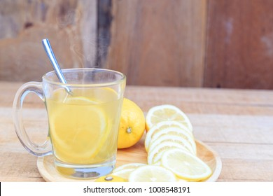 Drinking hot lemonade drink helps to heal the sick or cough or cold from the cold air in a glass with a spoon and slices of lemon on a natural wooden table with copy space.