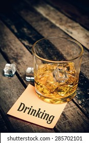 Drinking with label on paper note. Glass of scotch whiskey