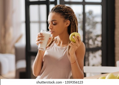 Drinking milk. Appealing fit woman wearing sport top drinking glass of milk and eating green apple