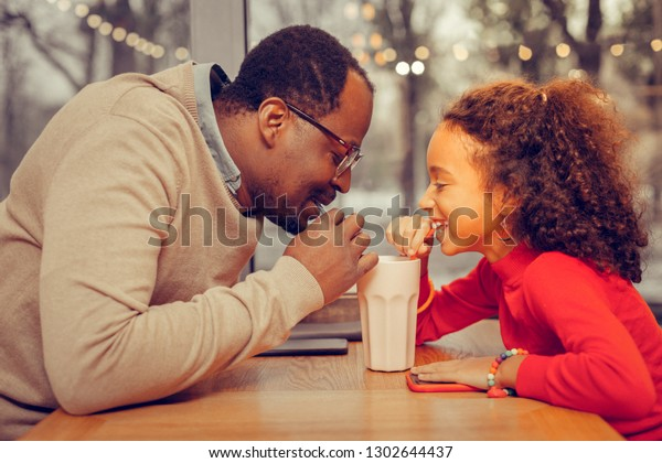 Drinking milk cocktail. Father and daughter drinking milk cocktail together in cafeteria